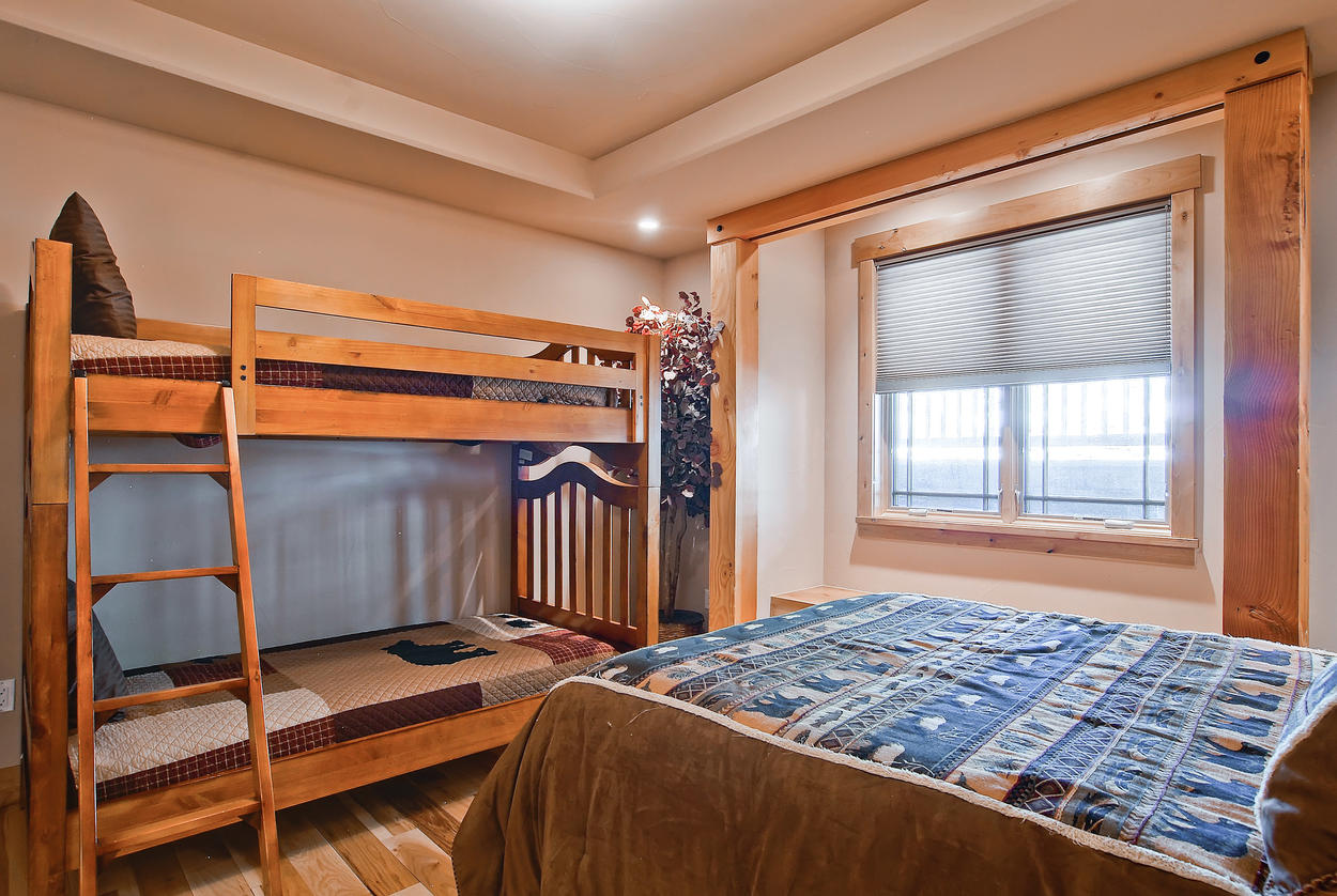 The main level Guest Bedroom 3 includes a queen bed and twin bunks, but only has access to a half bath powder room on this level.