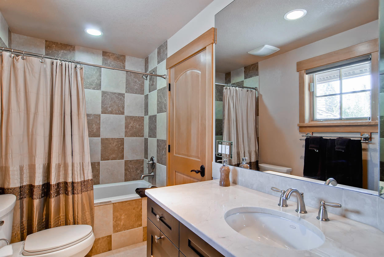 The private bathroom in the above garage suite has a tub/shower combo and single vanity.