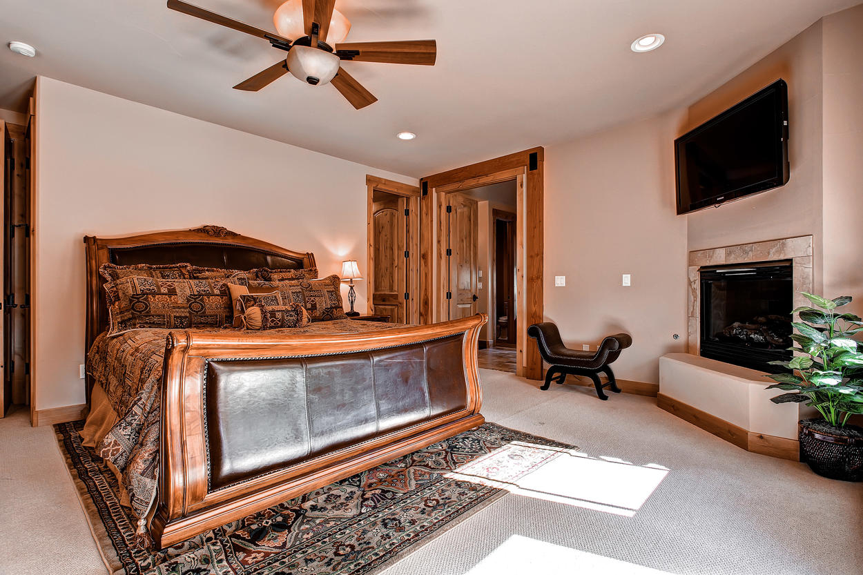 The main level Master Bedroom 1 features a king-size bed, TV, and its own fireplace.