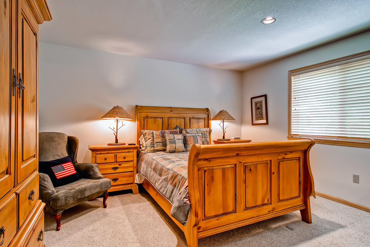 Bedroom 2, located on the main floor of the home. Features a queen bed, TV, and direct access to the hallway bathroom.