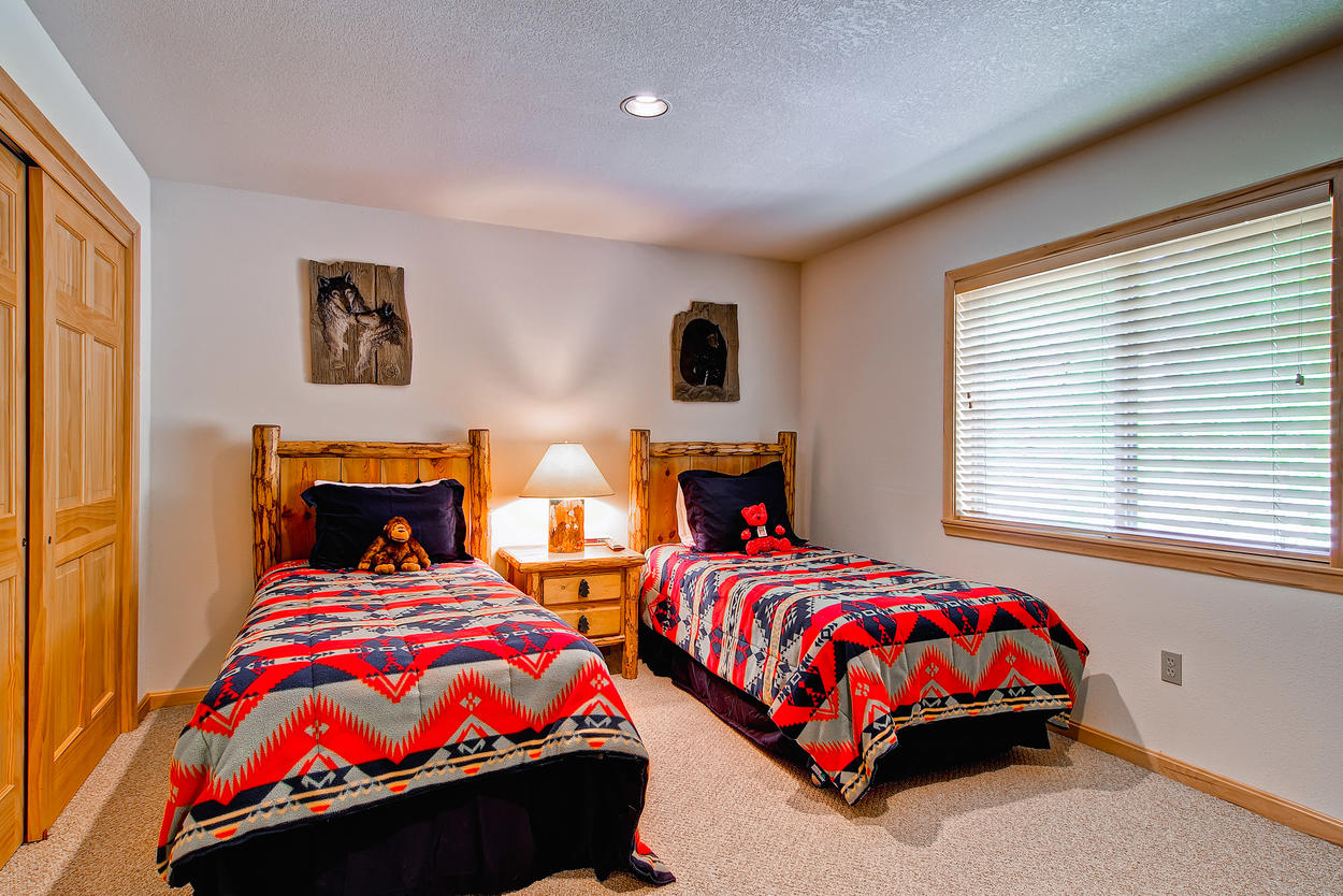 Lower level bedroom, features two twin beds, TV, and direct access to the hallway bathroom.