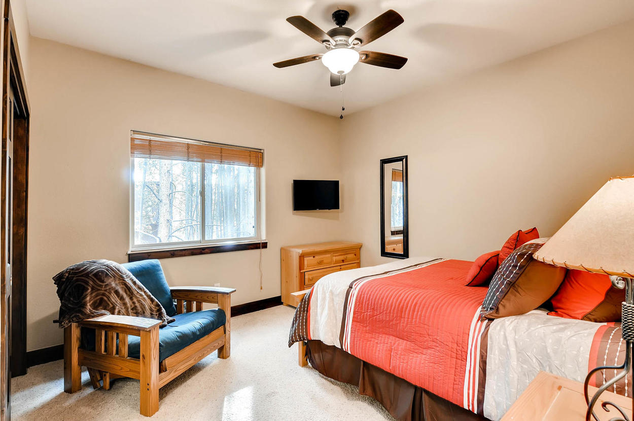 On the main floor, guest bedroom 2 has a queen bed and TV and shares a jack-and-jill bathroom with guest bedroom 3.
