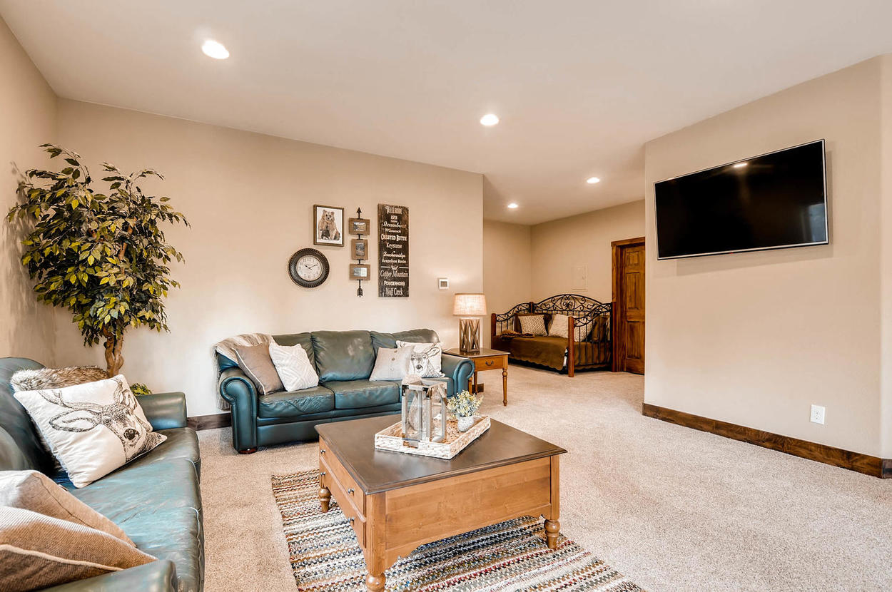 This downstairs den offers fun for the family. Sit back on one of the many leather couches and watch TV, make use of the pool table, or head to the back deck and take a soak in the hot tub.