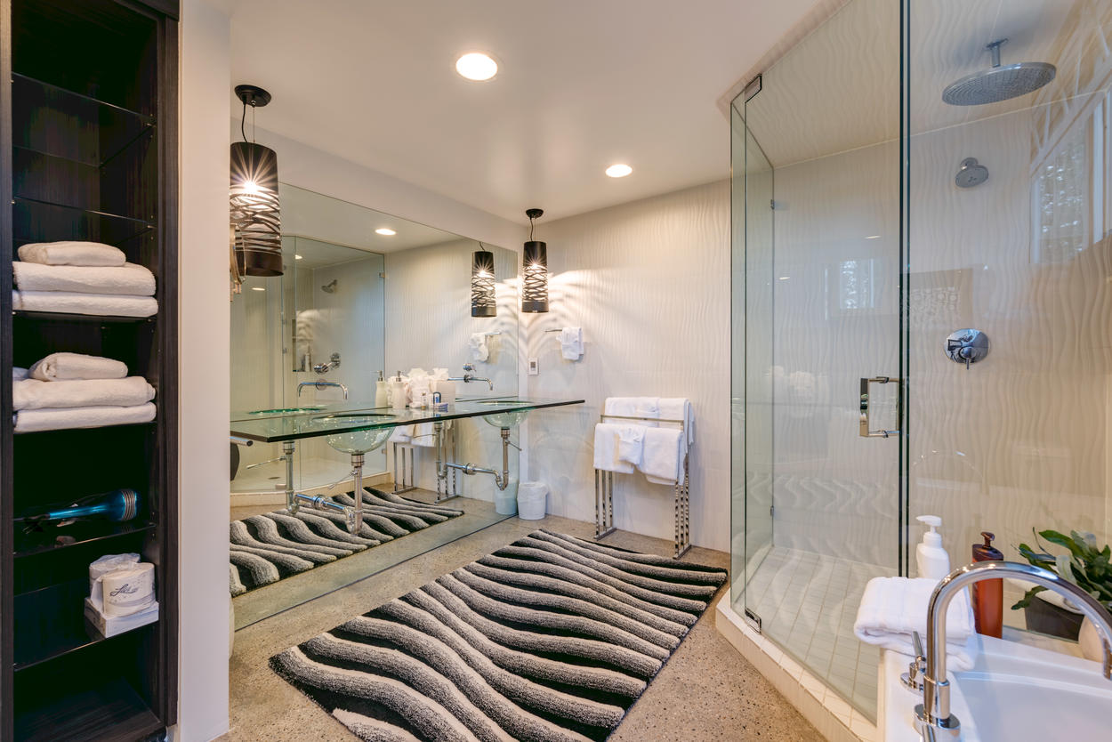 The exquisite glass vanity is an architectural marvel, and a highlight of the stunning Master Bathroom.