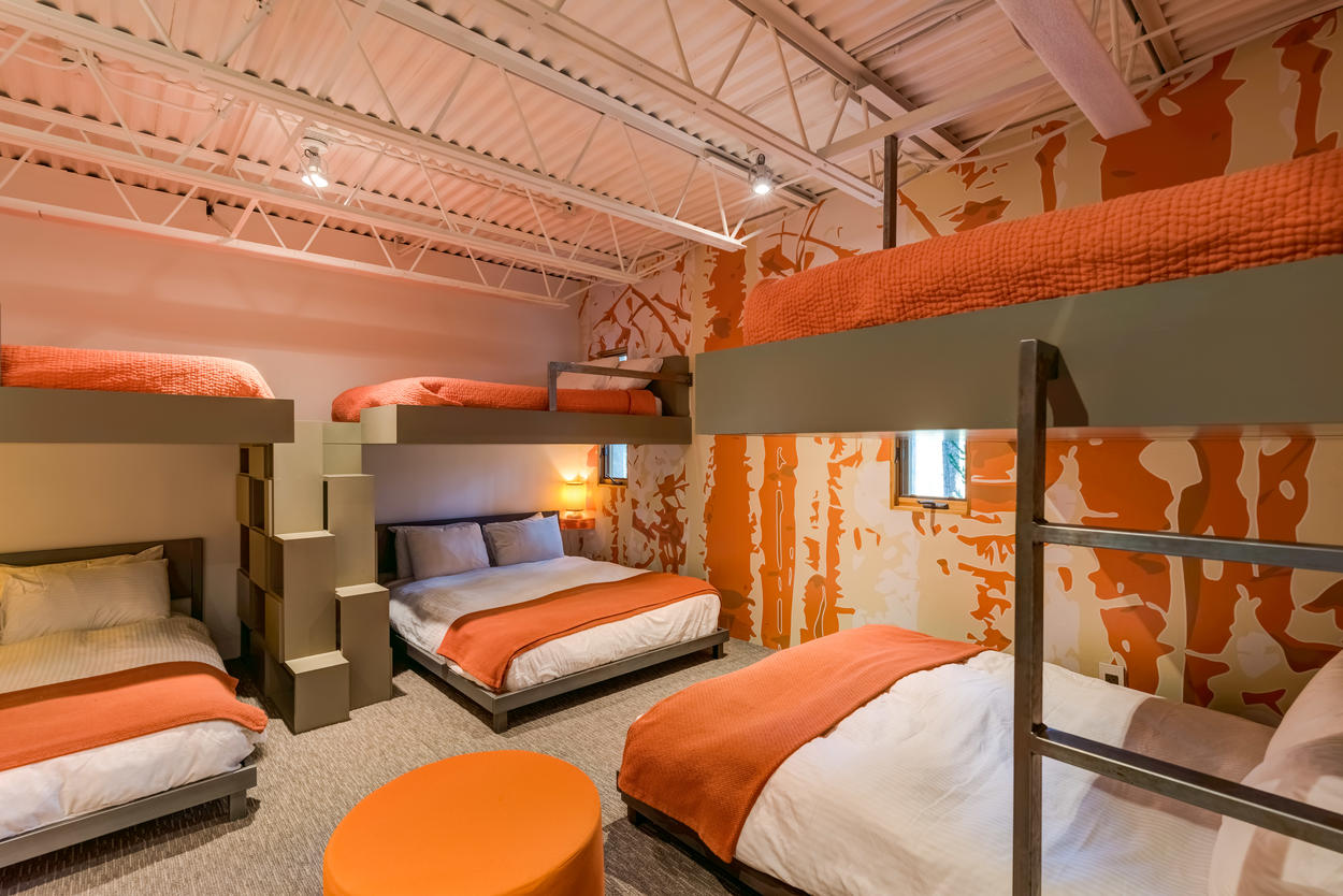 On the lower level, the bunk room has 6 beds: The 3 upper bunks are full-size beds, while the 3 lower beds are freestanding queen-size beds.