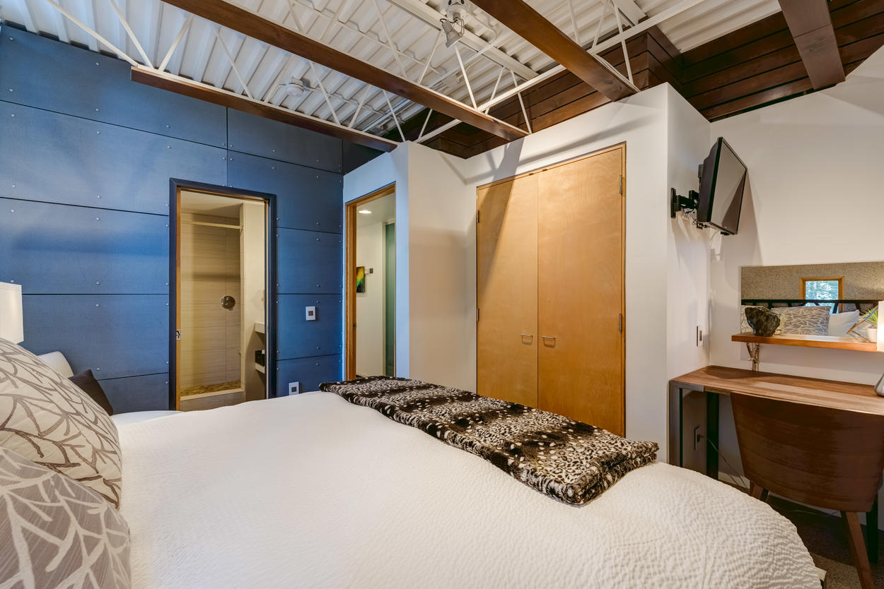 The upper level Pebble room comes with a king bed, a desk, and a spacious closet with built-in storage areas, and TV.