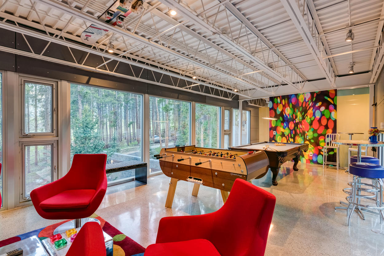 The game room on the upper floor is complete with a pool table, foosball and tons of amenities, including a coffee bar, games, a candy selection, Sonos speakers, a microwave, and a mini-fridge.