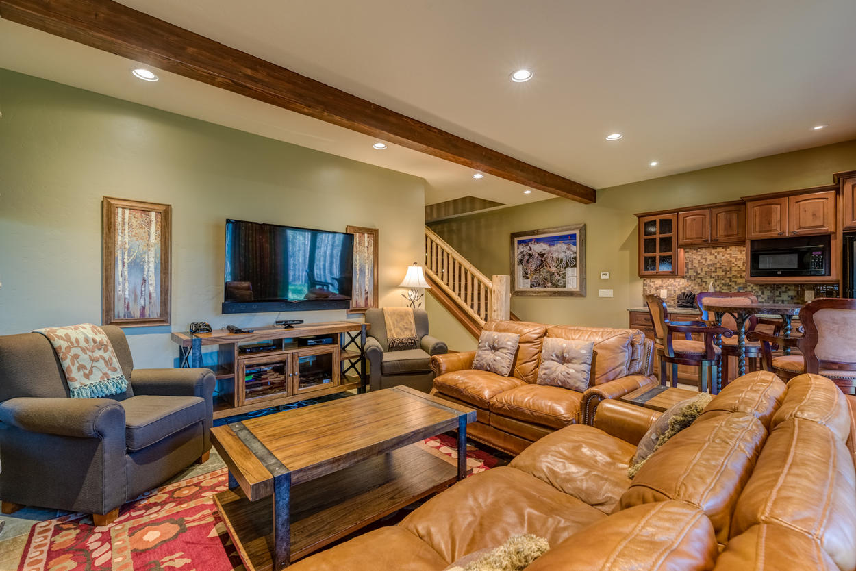Downstairs on the lower level there's a cozy den with couches, chairs, a large TV, and a kitchenette.