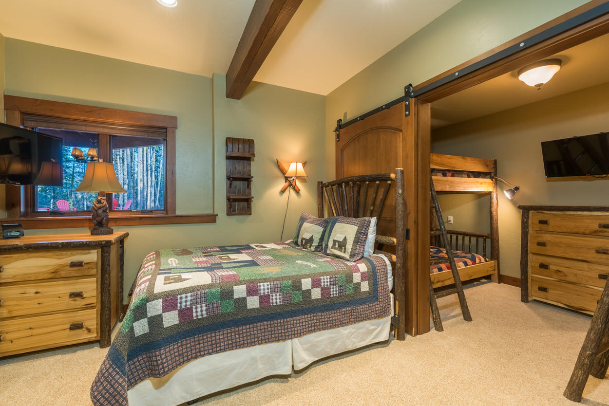 In the lower level bedroom, there's a single queen-size bed and two sets of twin bunks.