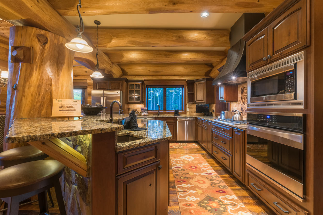The kitchen is filled with stainless steel appliances, including an oven, microwave, gas stove, and dishwasher.