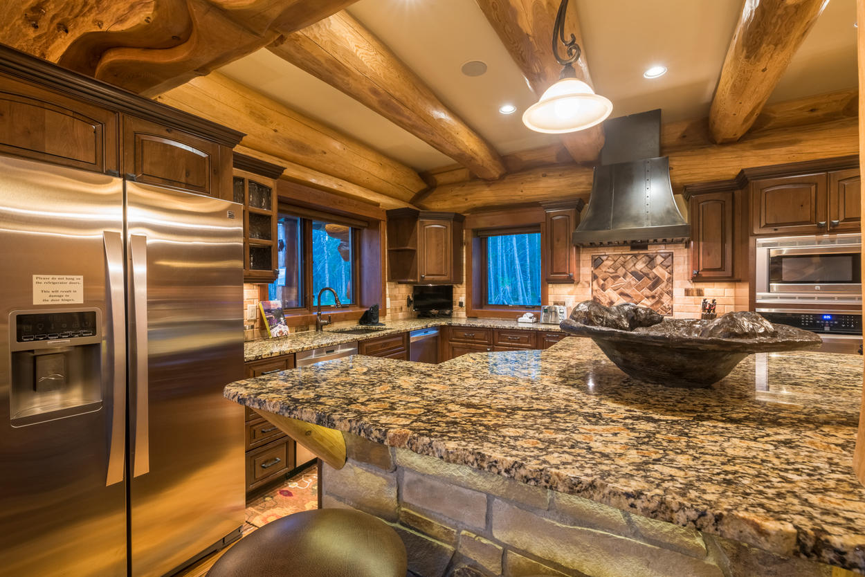 A large and stately range hood is set above an elaborate tile backsplash in the kitchen.