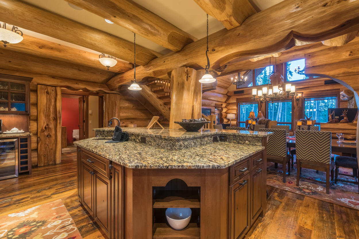 The tiered kitchen island is topped with chiseled granite, and includes fine woodwork below.