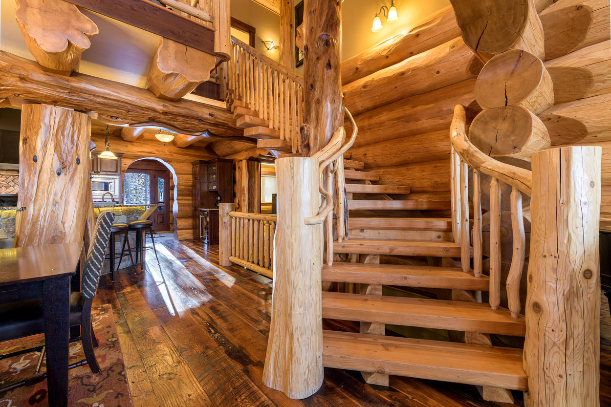 An intricate wooden staircase leads to the loft and upper bedrooms.