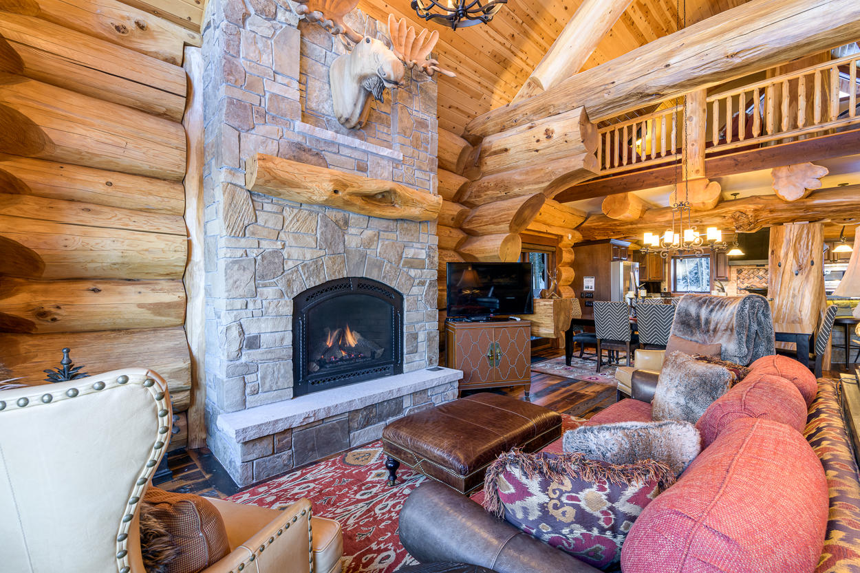 The great room has a traditional stone fireplace, plenty of seating, and a flat screen TV.