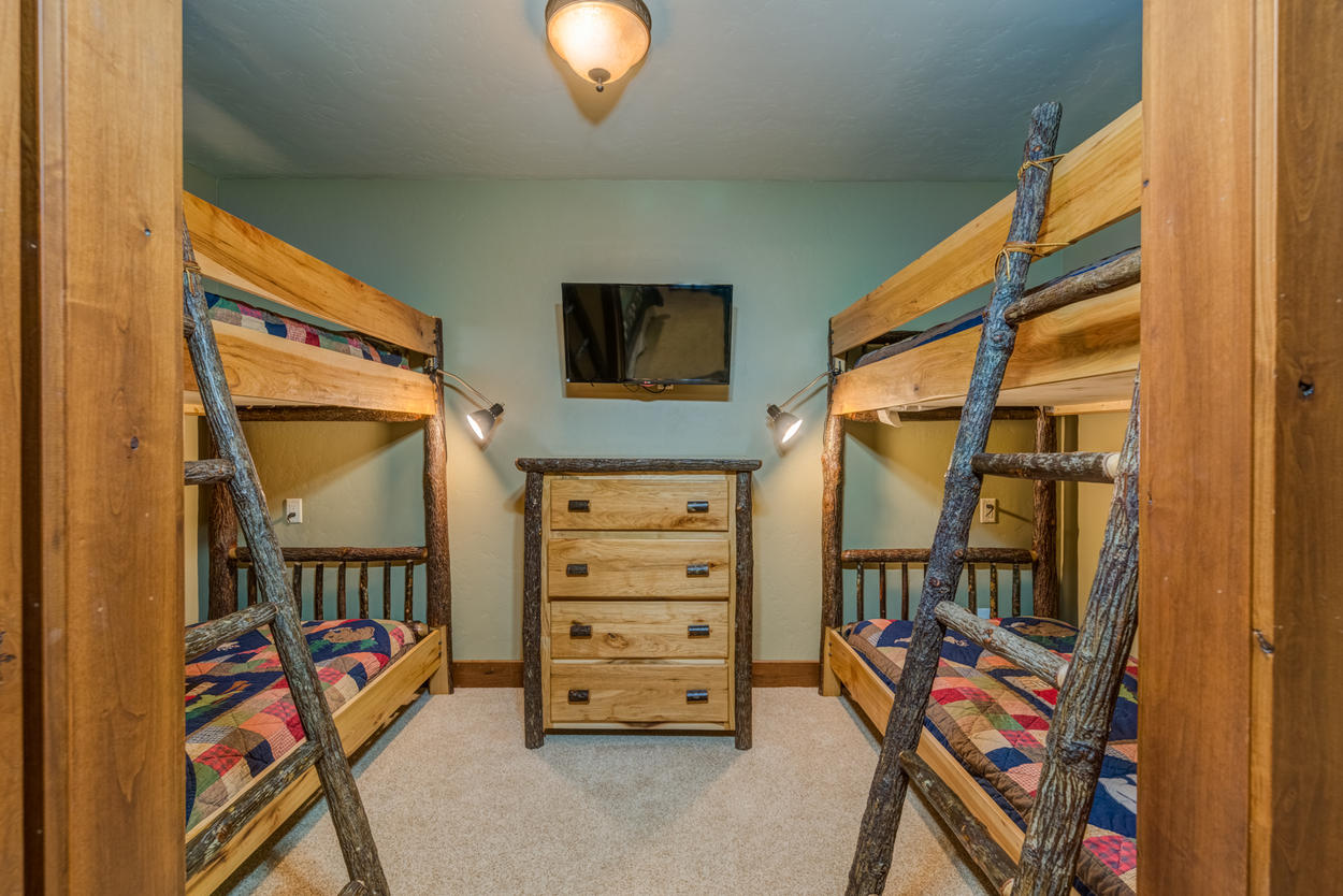 The fourth guest bedroom has a twin bunk area, closed off by a sliding barn door.