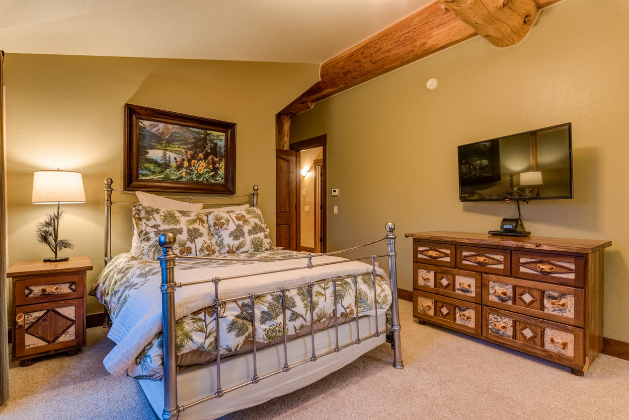 The second guest bedroom, on the upper level, has a queen-size bed and a mounted TV.