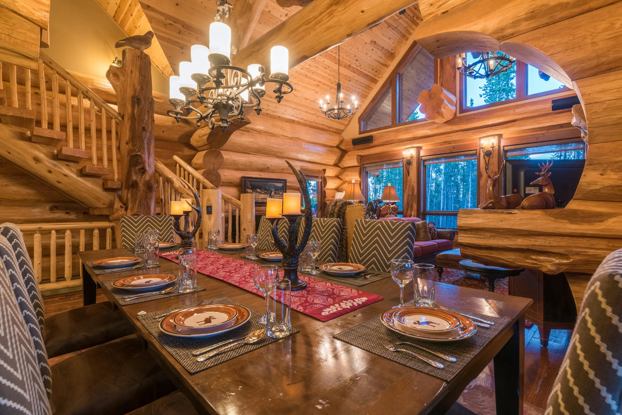 The dining table is set under a classic chandelier and adorned with traditional mountain decor.