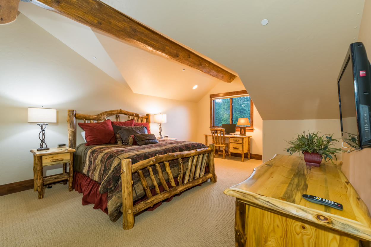 On the upper level, Guest Bedroom 2 features a king-size bed, an office nook, and TV.