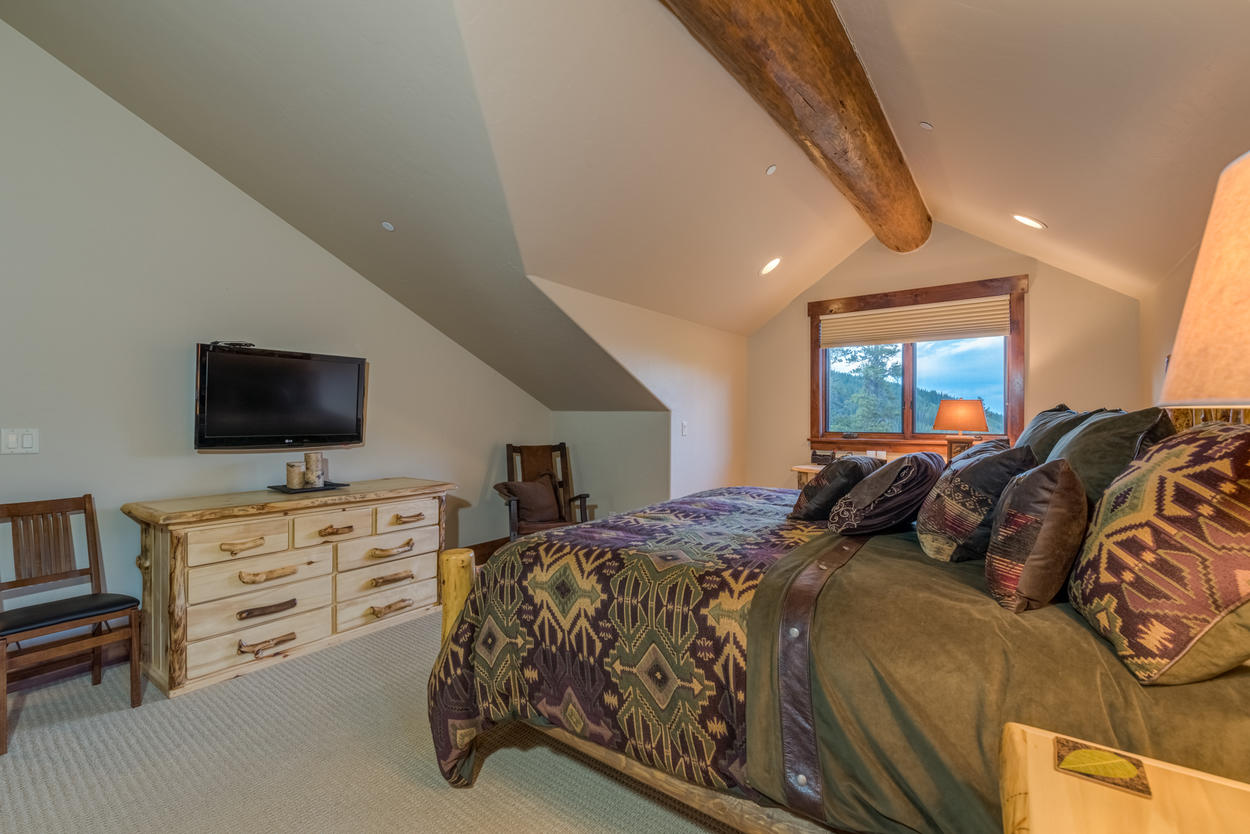 This upper level bedroom offers stunning views from the window of the surrounding mountains.
