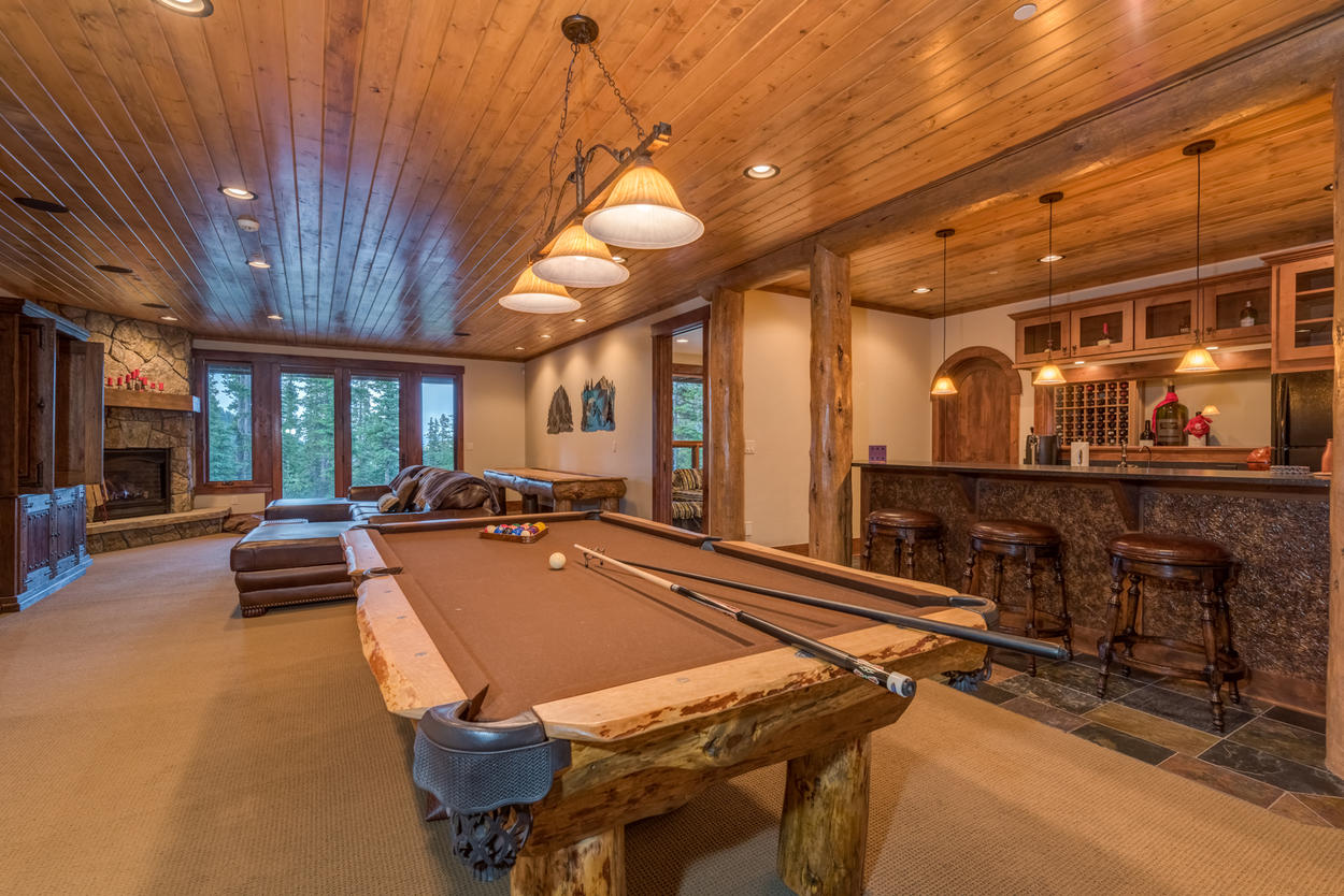 Wander down to the lower level to find the game room, complete with pool table, kitchenette bar, TV, and gas fireplace.