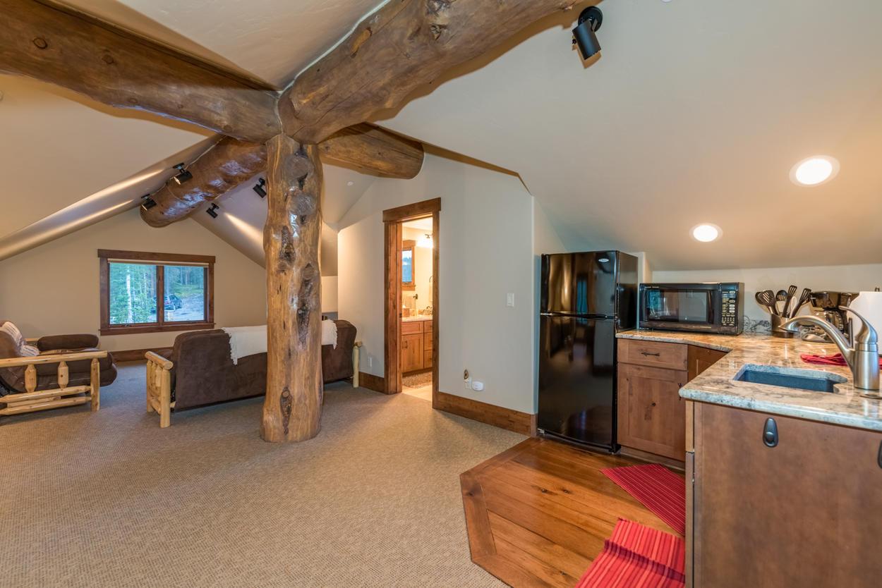 The apartment above the garage is a large open-concept space with massive exposed wood beams.