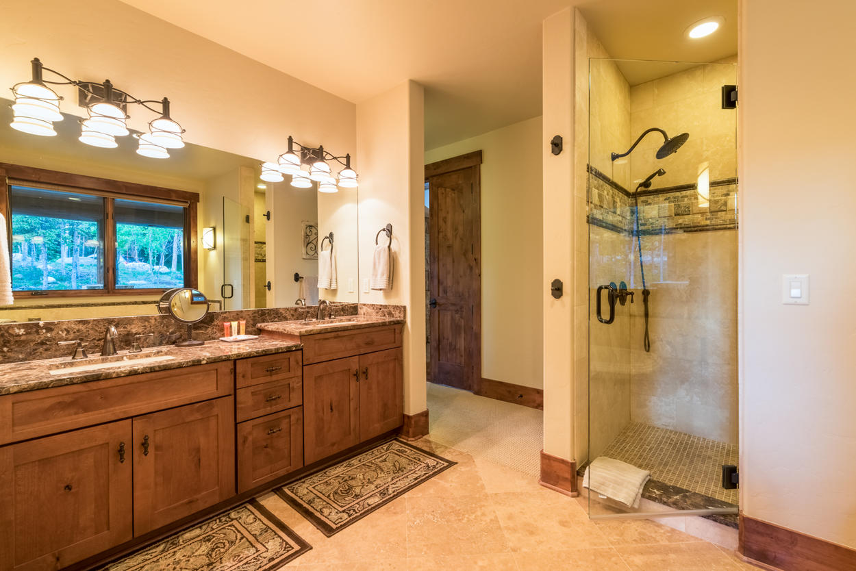 The large ensuite Master Bathroom features a double vanity with plenty of lighting, walk-in shower, and bathtub.