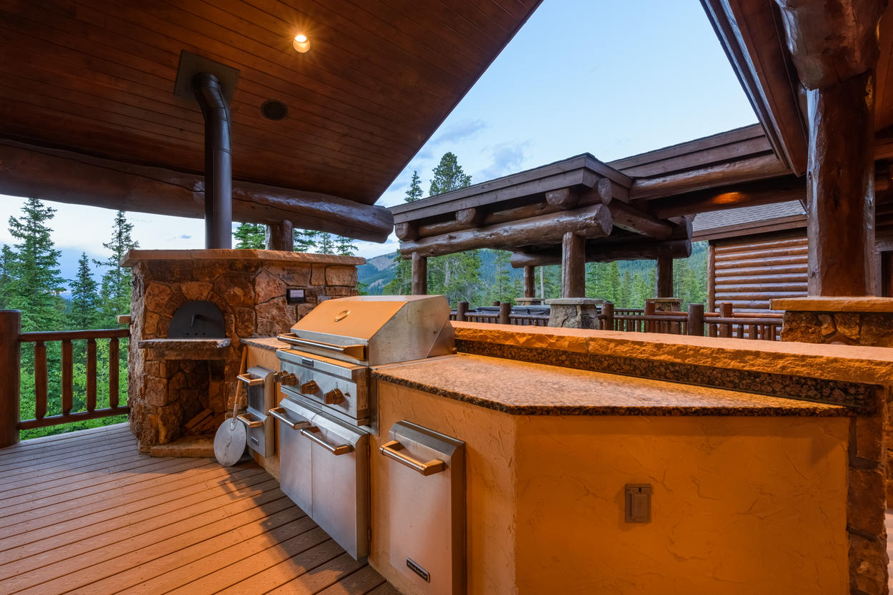 Outdoor built-in grill and pizza oven on spacious wrap around deck.