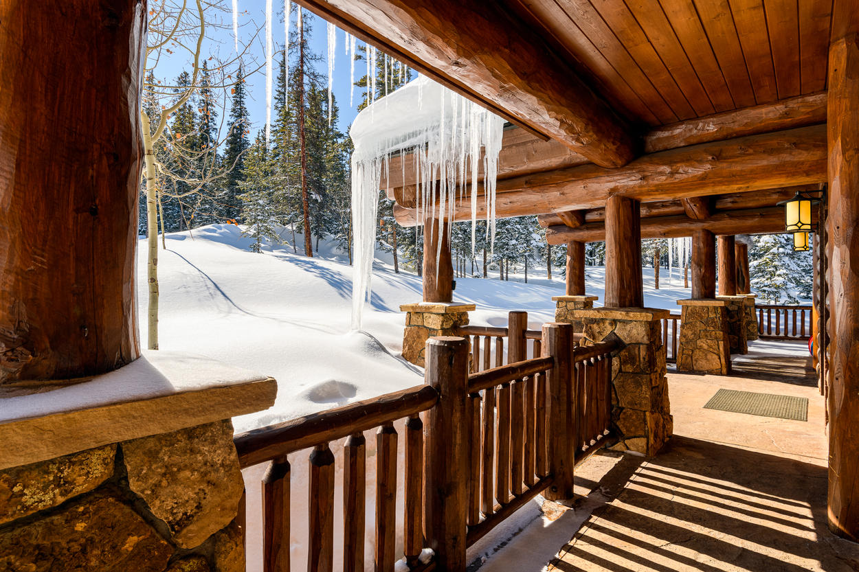 Walk the path to the front foyer and you'll notice the huge wood beams that compose the log cabin design