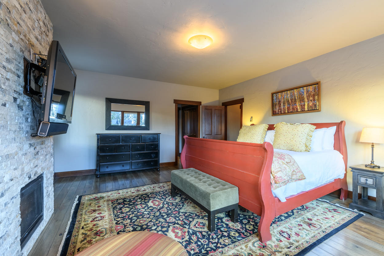 The Master Suite features a king bed and wall-mounted flat-screen TV, and gas fireplace.