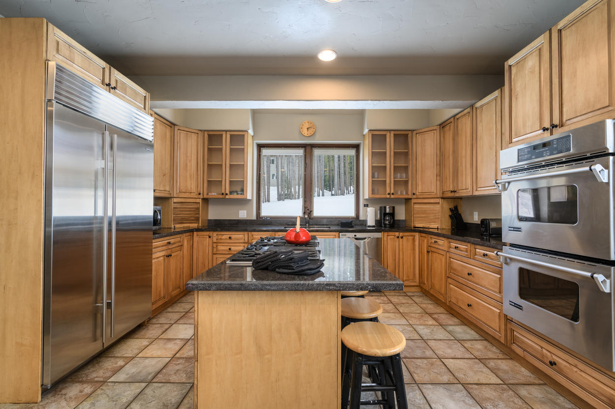 The kitchen includes stainless steel appliances, such as a double oven and large refrigerator.