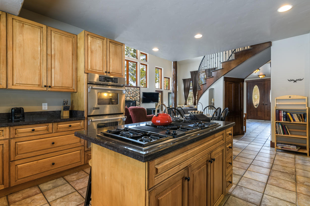 An island in the kitchen has a 6-burner gas stove and seating for four guests.