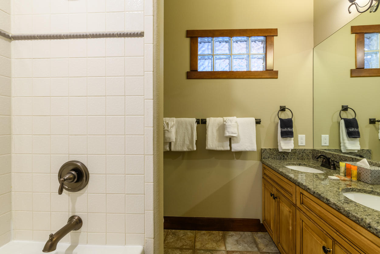 The top floor has a shared bathroom with two sinks and a shower/tub combination for guest bedrooms 3 and 4.