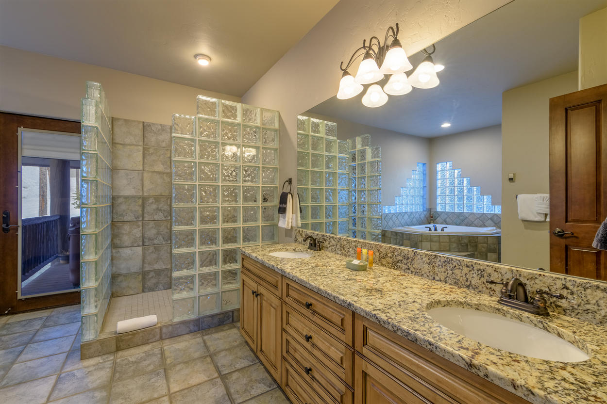 The Master Ensuite has a large double vanity and walk-in glass block shower. A large jetted tub is located in the corner.