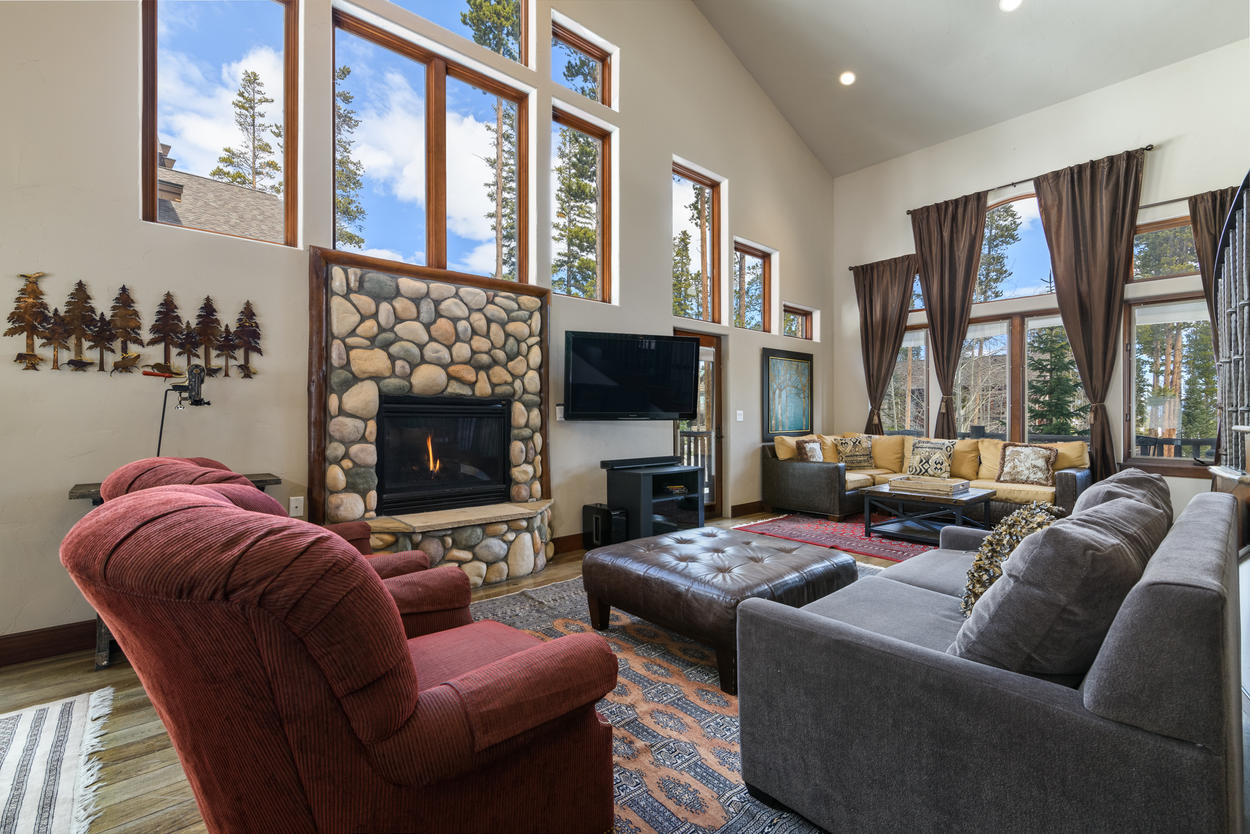 The main living area features a gas fireplace and river rock chimney.