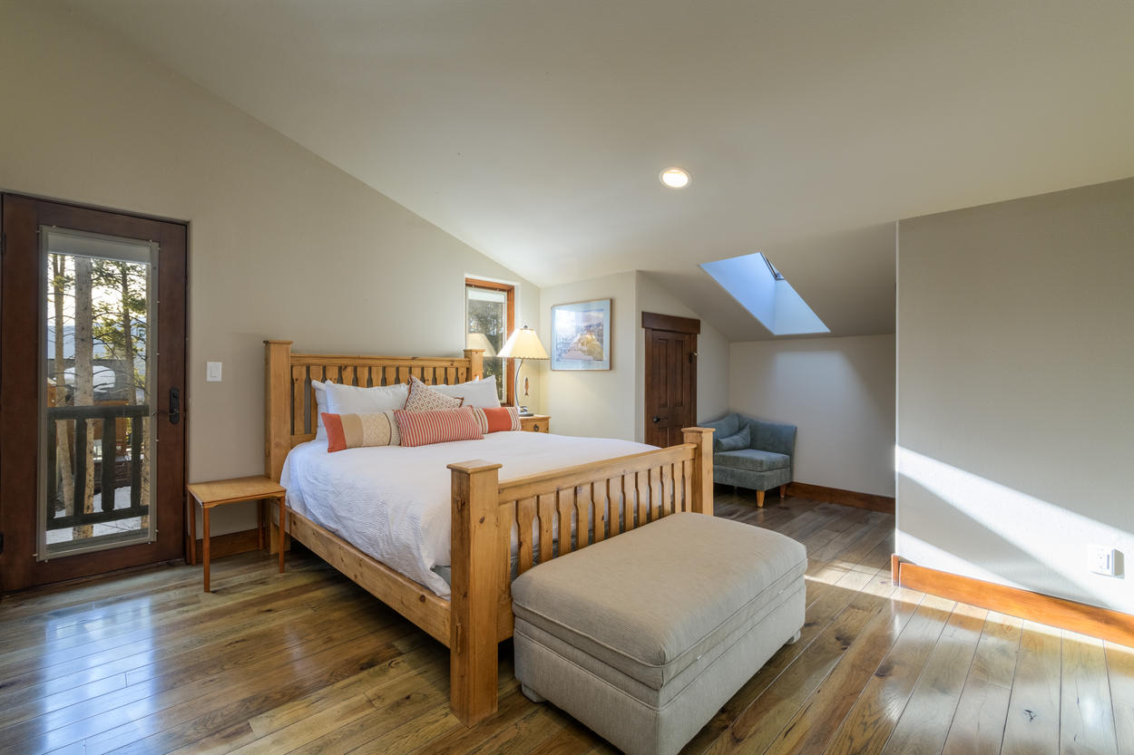 Guest bedroom 3, located on the top level, has a queen bed and access to a balcony and outdoor bistro set.