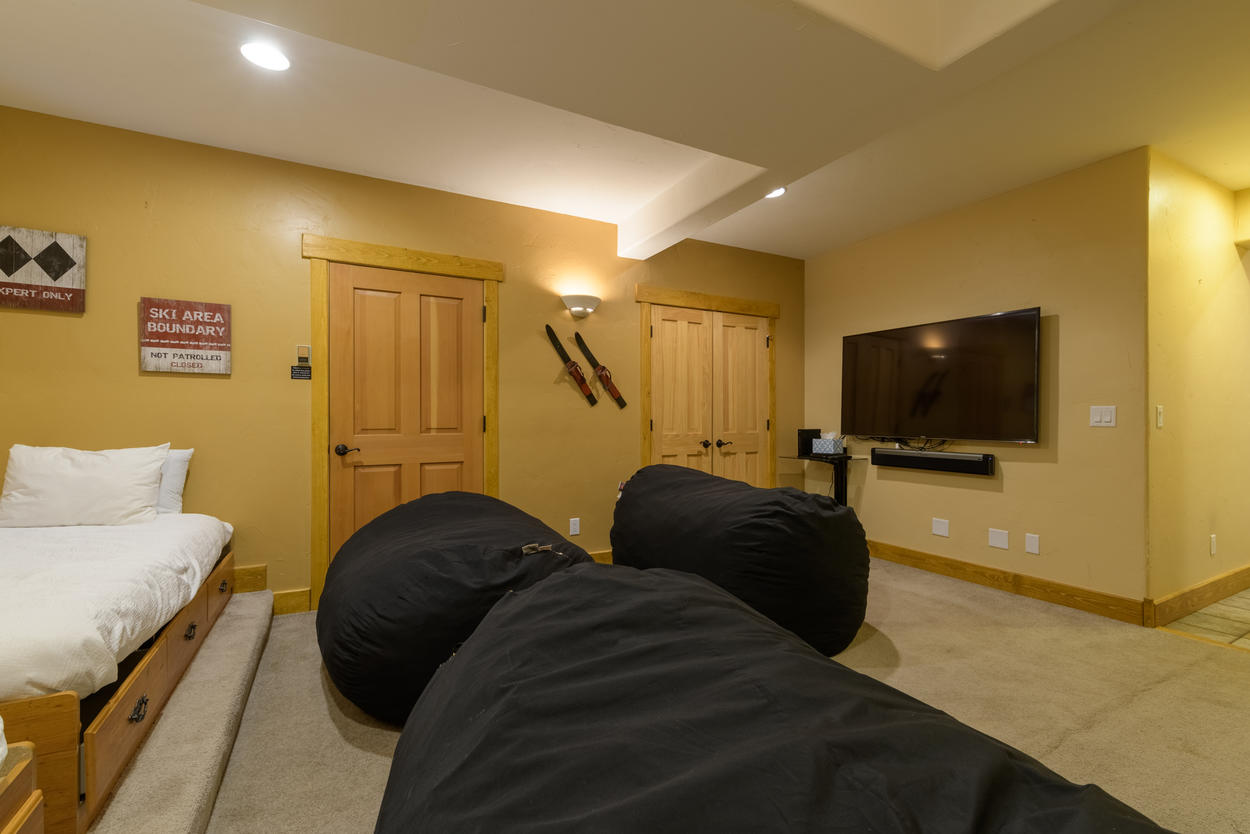 The TV room, located on the lower level, has three oversized bean bag chairs and two twin beds.