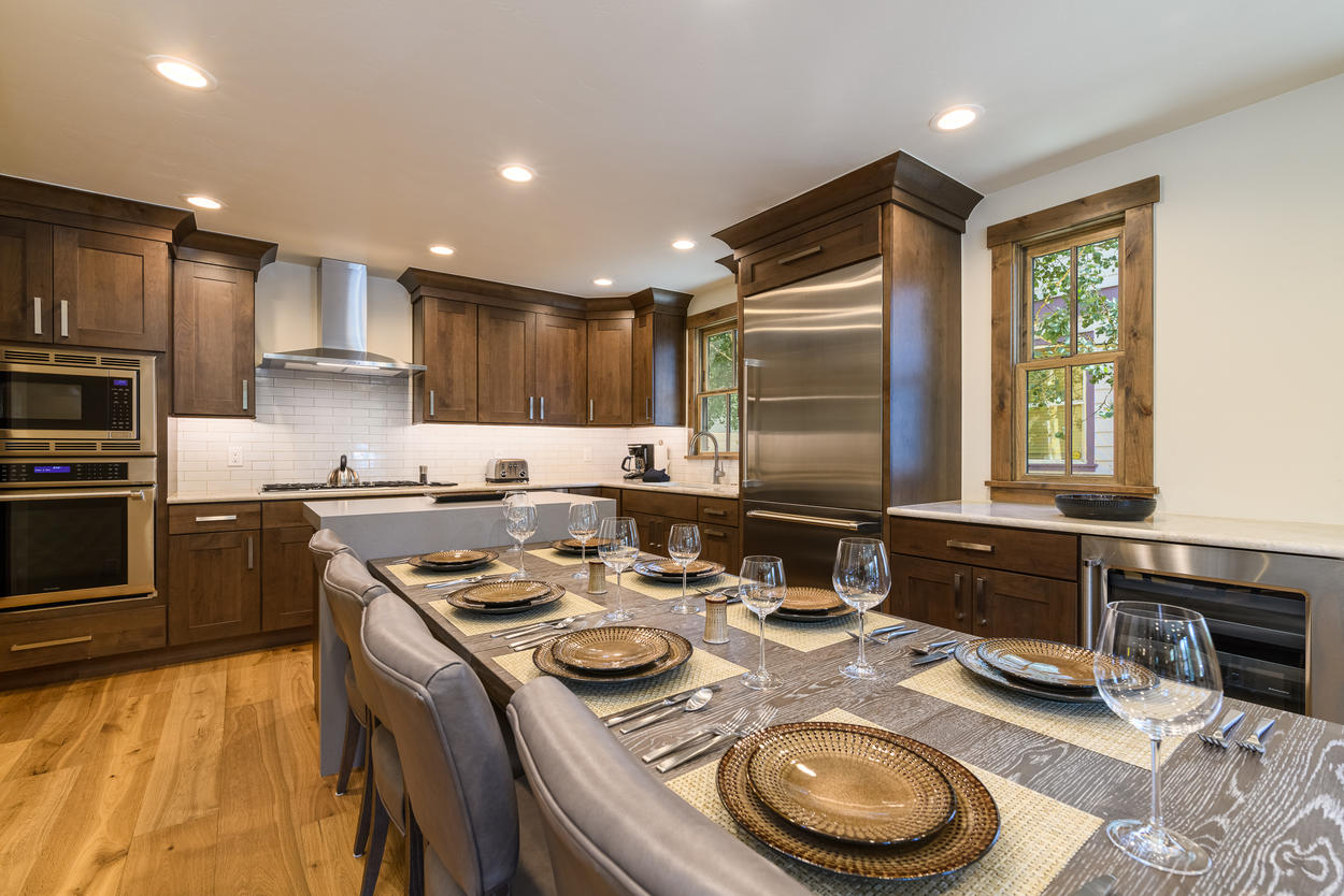 The dining table is a part of the kitchen's open-concept design.