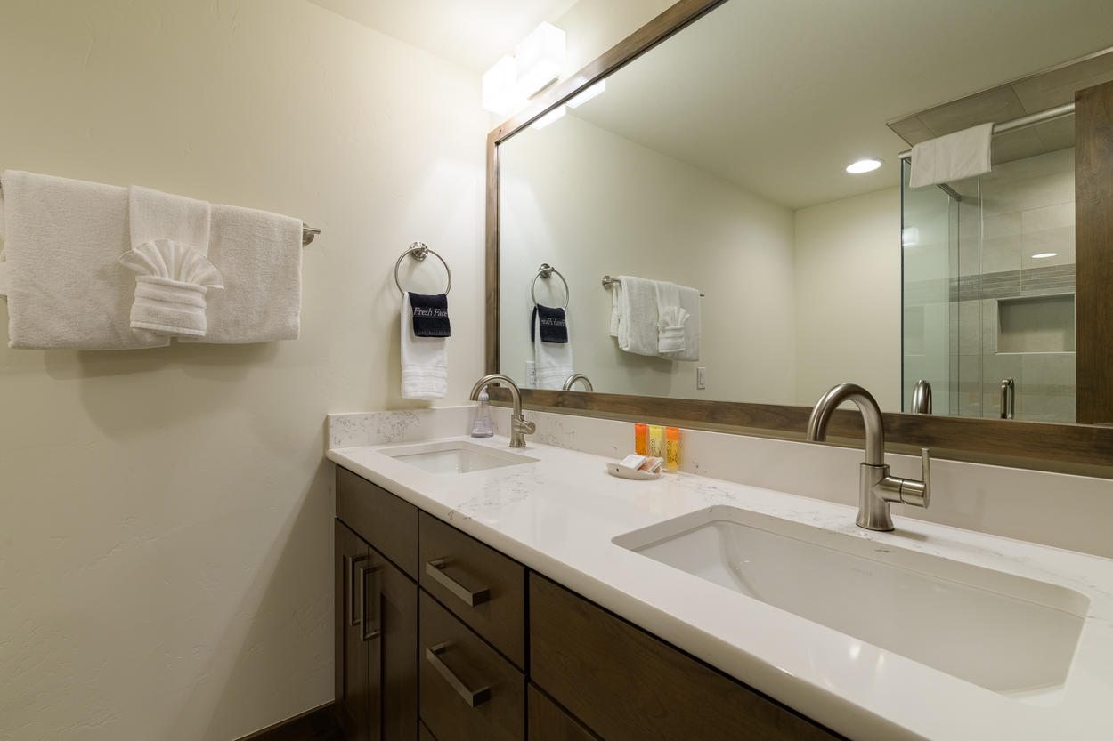 The ensuite bathroom for the bunk bedroom has a walk in shower and double sink vanity.
