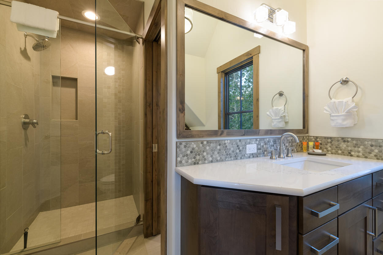 The master bathroom features a spacious walk-in shower, and two stand-alone vanities.
