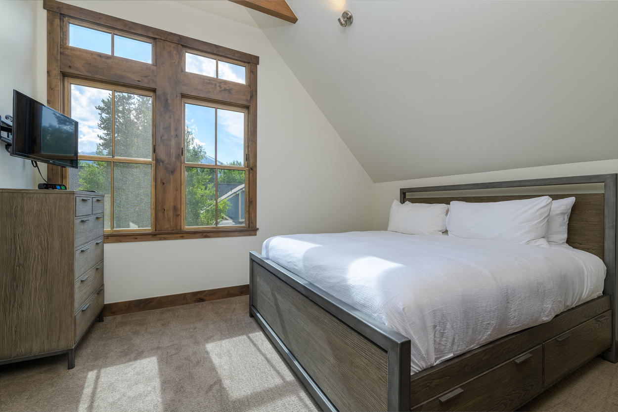The master bedroom is located on the second level and features a king bed and a TV.