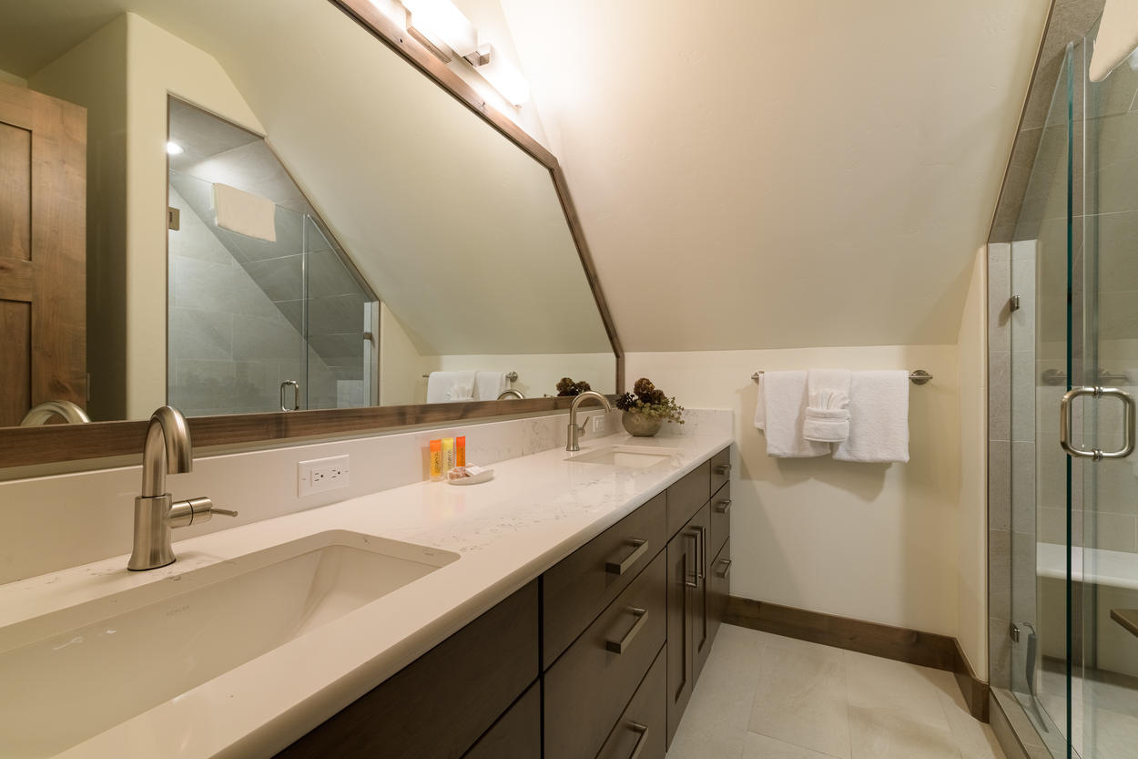 The ensuite bathroom for Guest Bedroom 2 features a walk-in shower and dual vanity.