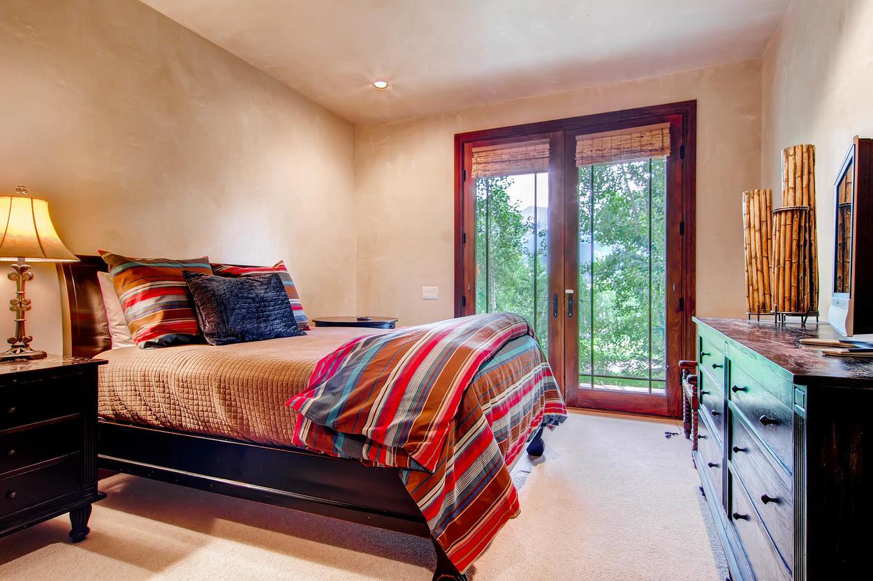 Guest Bedroom #3 has a queen bed and a big flatscreen TV.