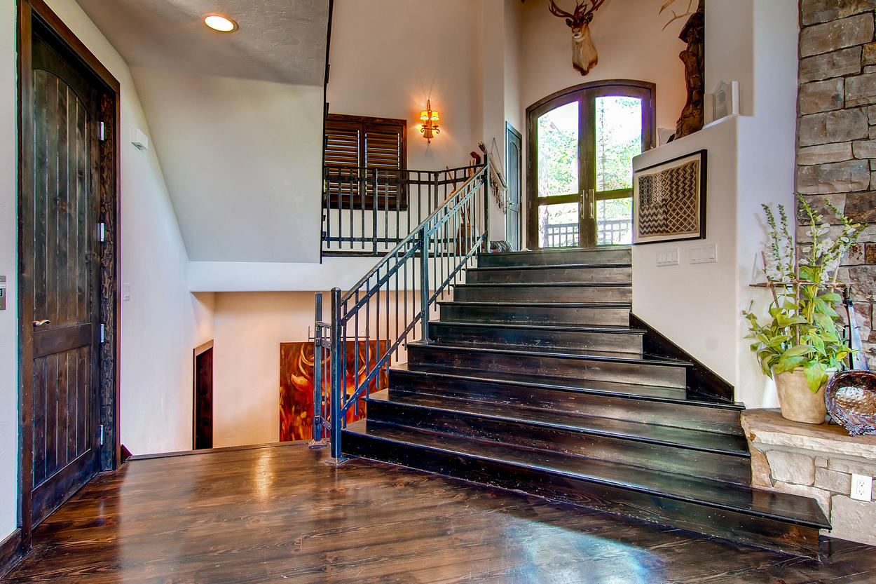 The grand staircase in the main entryway lead up to the upper level and lower levels below.