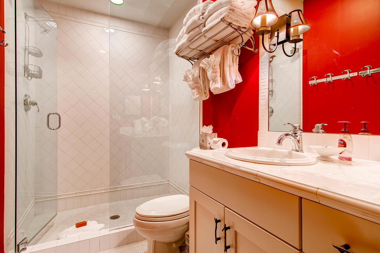 This guest bathroom features a walk-in shower and marble countertops.