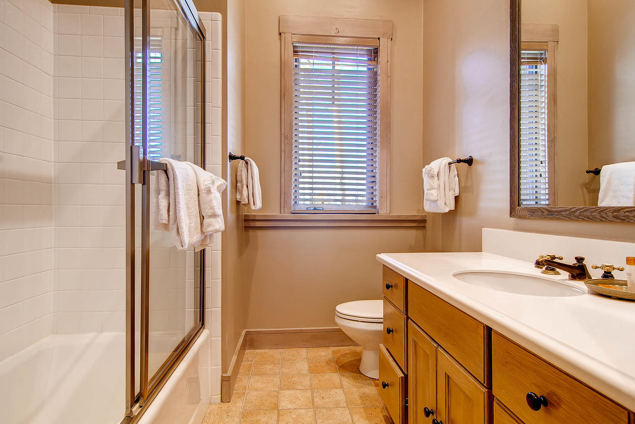 The en suite bathroom for Guest Bedroom 4 features a shower/tub combo and single sink vanity.