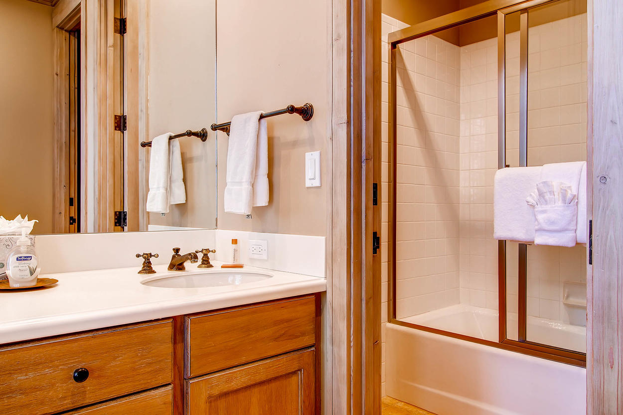 The ensuite bathroom for Guest Bedroom 2 features a shower/tub combo.