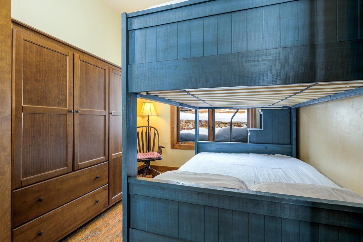 The guest bedroom features an oversized bunk set, with a full bed on both the top and bottom.