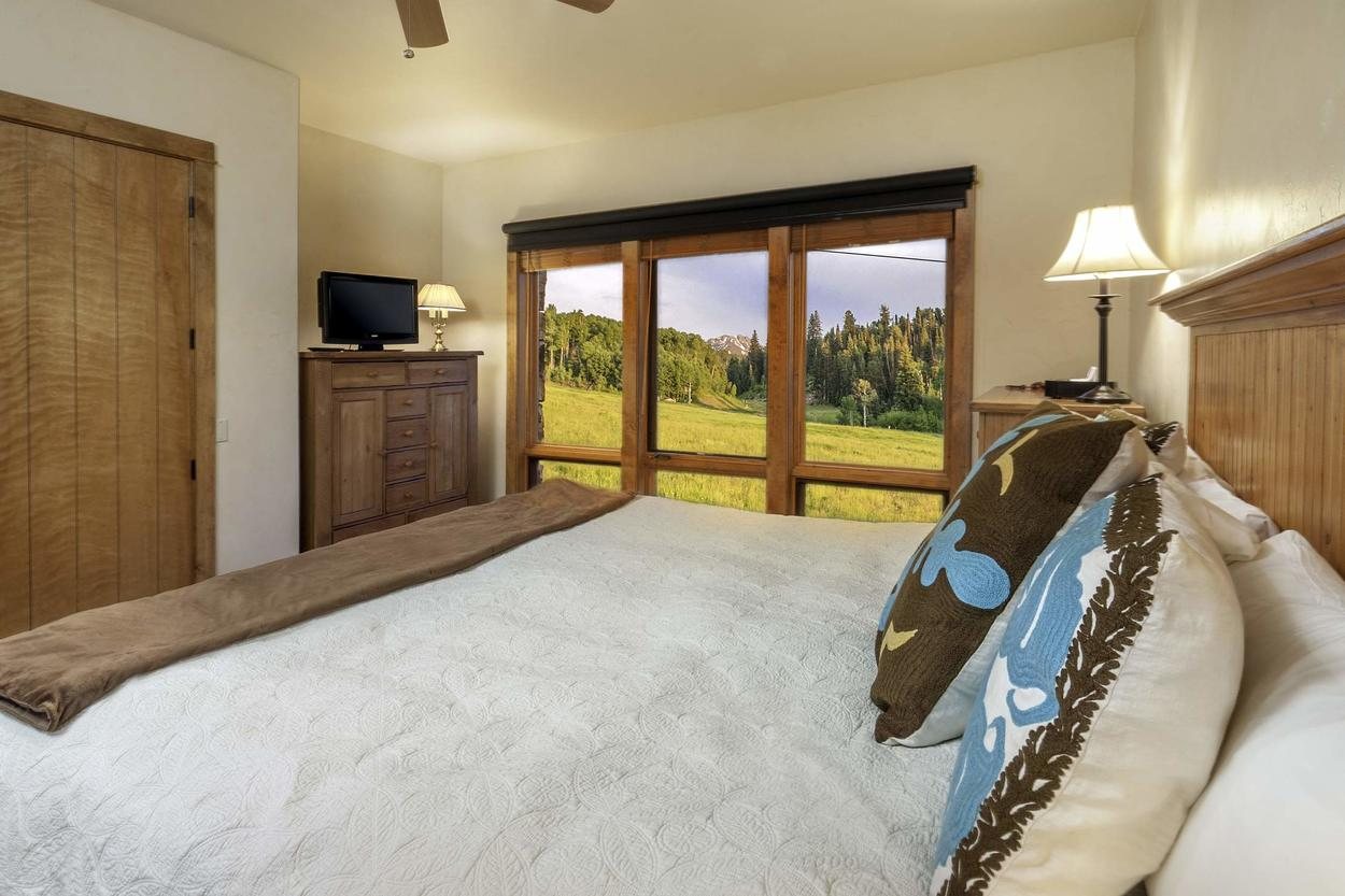 The master bedroom features a king-size bed, TV, and a view of the slopes outside.