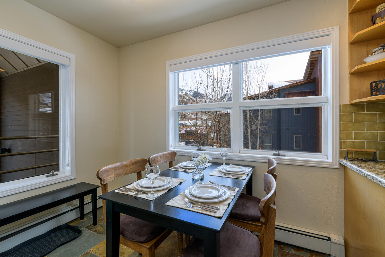 The dining table for four has plenty of natural light through the windows.