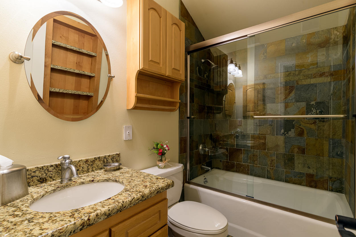The second floor bathroom has a tub/shower combo and a vanity with granite countertops.